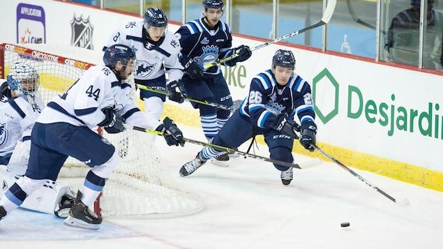 Des joueurs de hockey se disputent la rondelle derrière le filet.