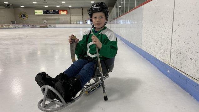 Tyler est assis avec les jambes devant lui sur une petite luge sur une patinoire dans un aréna. Il tient deux petits ba^tons de hockey dans ses mains.