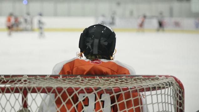 Un enfant est gardien de but de hockey. Il est de dos et fait face au reste des joueurs sur une patinoire intérieure (archives).