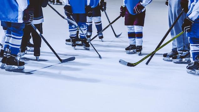 Les patins et les bâtons de jeunes joueurs sur une patinoire