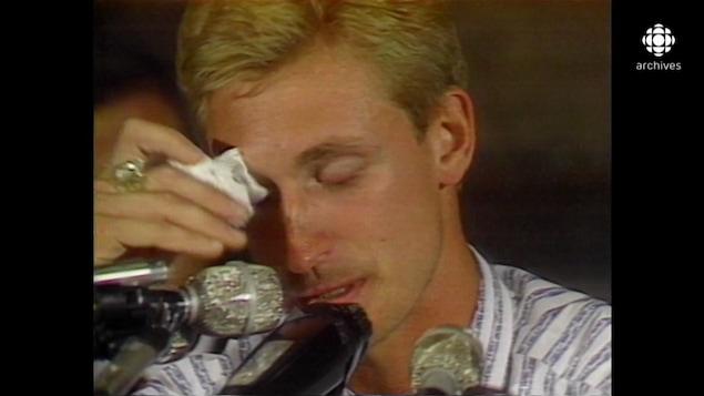 Gros plan sur Wayne Gretzky s'essuyant les yeux devant les micros à la conférence de presse annonçant son échange.