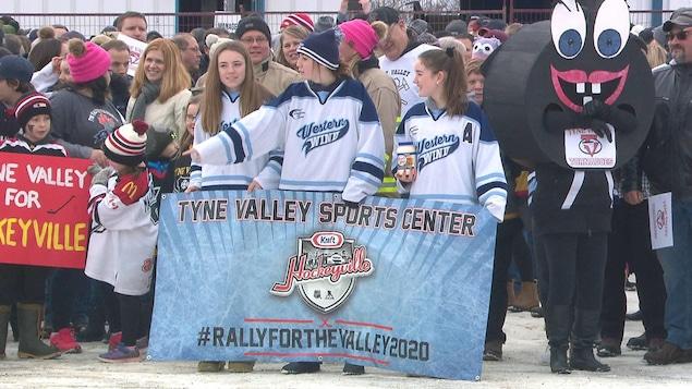 Des jeunes avec une bannière et une mascotte en forme de rondelle de hockey avec une bouche.