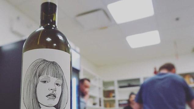 Une bouteille de vin en avant plan, une équipe de cuisinier qui discutent en arrière plan.