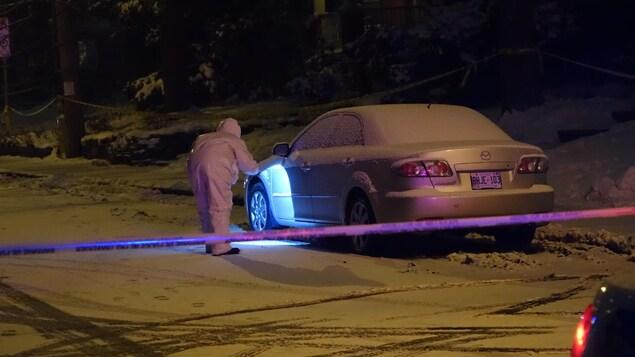 Un enquêteur revêtu de blanc observe attentivement une voiture.