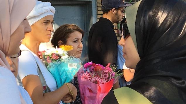 Des femmes voilées tiennent des bouquets de fleurs, en attente de la cérémonie à la mémoire de la cycliste morte le 14 juillet.