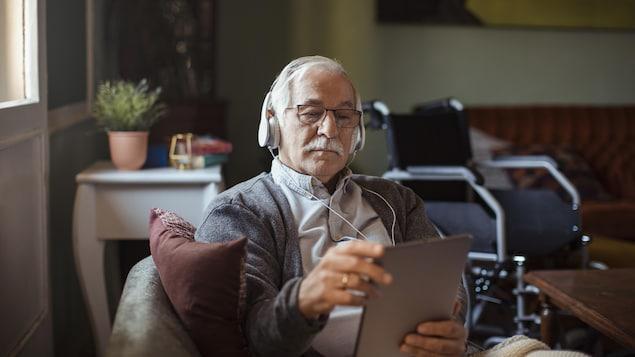 Un homme âgé écoute de la musique à partir de sa tablette.