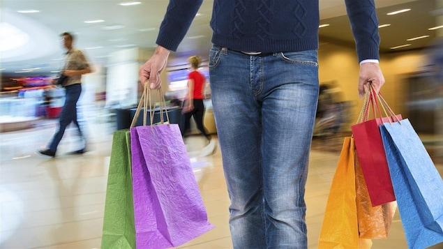 Un homme porte des sacs dans un centre commercial.