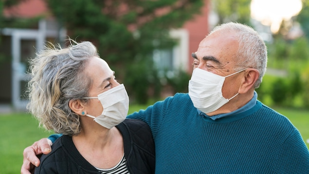 Un homme et une femme portent des masques.