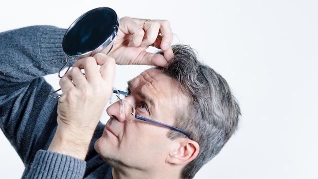 Un homme cherche des cheveux blancs avec un miroir.