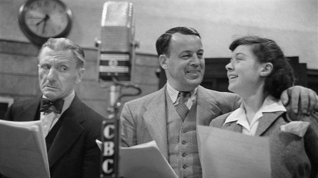 Dans un studio de radio, Hector Charland, Albert Duquesne, celui d'Alexis ainsi qu'Estelle Mauffette sont debout, côte à côte, leurs textes à la main, derrière un micro sur pied.