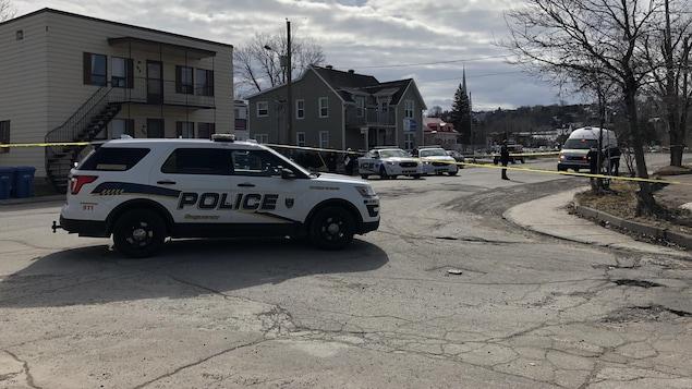 Un périmètre policier et des autopatrouilles devant des immeubles à logement