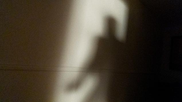 L'ombre d'un homme est projetée sur un mur.