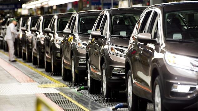 Un travailleur inspecte les véhicules à l'usine de Honda.