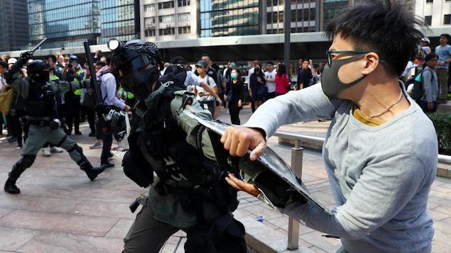 Un manifestant agrippe le bouclier d'un policier antiémeute, qui brandit une matraque.