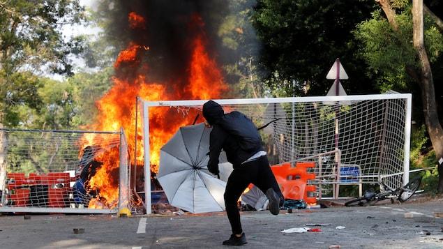 Un étudiant universitaire jette un objet à la police antiémeute.