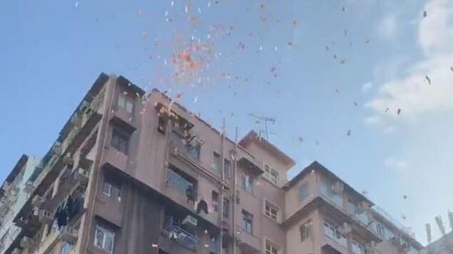 Des billets de banque sont lancés du haut du balcon d'un appartement au sommet d'un édifice à logements de plusieurs étages.