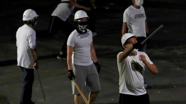Des hommes en t-shirt portent des masques et des casques. La plupart sont armés de bâtons.
