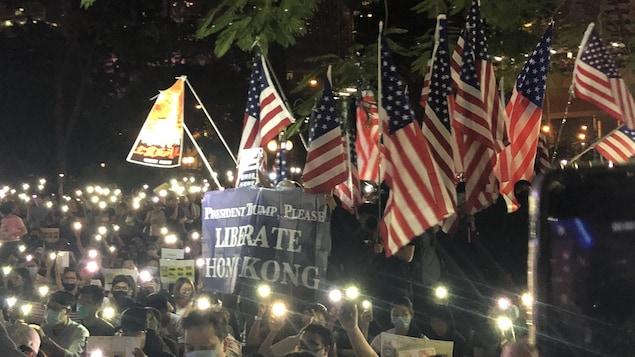Des manifestants réunis le soir avec des bougies et des drapeaux américains.