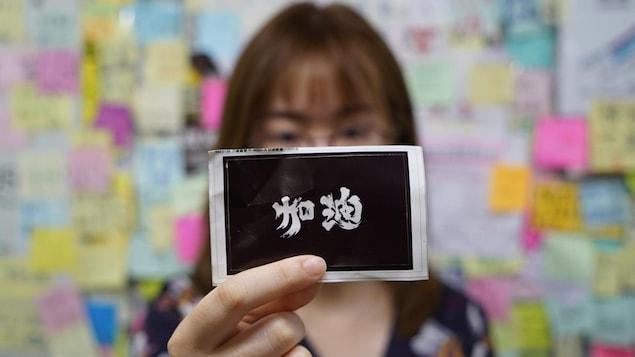 Une manifestante tient une étiquette sur laquelle il est écrit un message en cantonais.