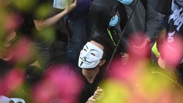 Des gens masqués sont rassemblés.