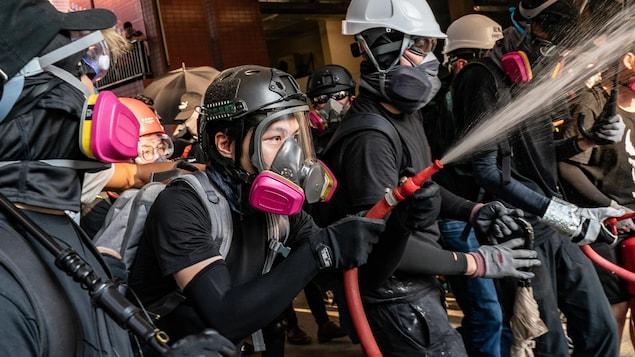 Des manifestants sont masqués et portent des casques.