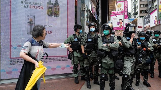 Une femme interpelle des policiers en tenue anti-émeute dans une rue de Hong Kong.
