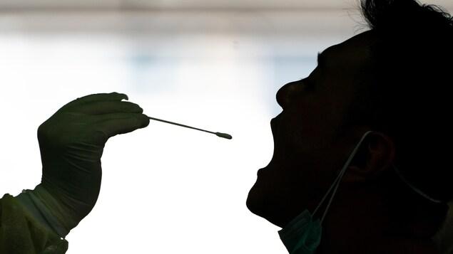 Un homme a la bouche ouverte. Une main gantée s'approche pour y insérer un écouvillon.