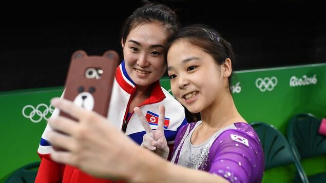 Deux fillettes se prennent en photo avec leur téléphone cellulaire.