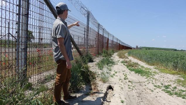 Un homme devant une clôture surmontée de barbelés, qui s'étire à perte de vue