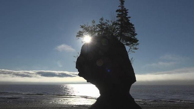 Le Soleil se couche derrière un rocher devant la baie de Fundy