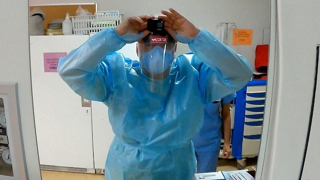 Le Dr Patrick Bellemare se regarde dans le miroir afin de s'assurer que sa caméra enregistre.