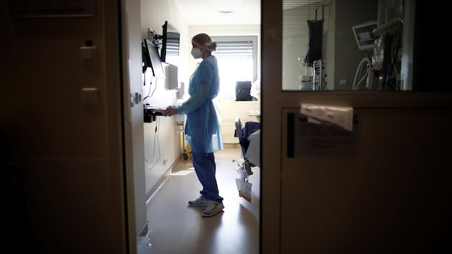 Une infirmière aperçue par la porte entrabâillée de l'unité des soins intensifs d'un hôpital.