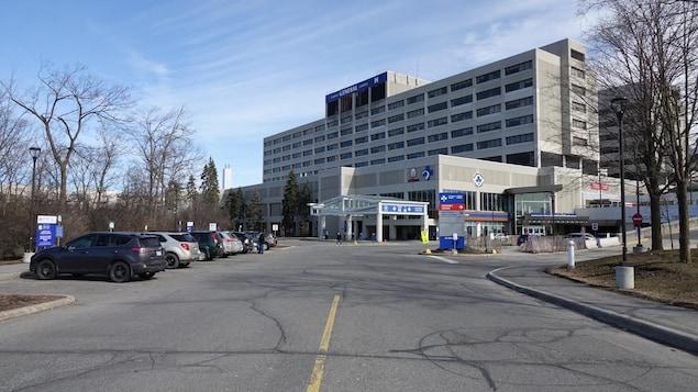 Gros plan de l'édifice avec voitures stationnées à gauche de l'entrée principale.