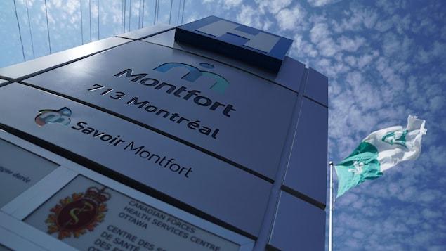 Un panneau de l'Hôpital Montfort près d'un drapeau franco-ontarien battant au vent.