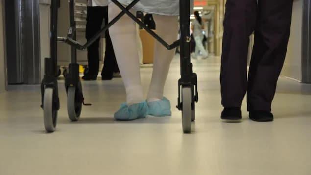 Un patient et son accompagnateur marchent dans un hôpital.