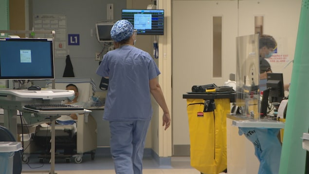Une infirmière marche dans une aile à l'hôpital.