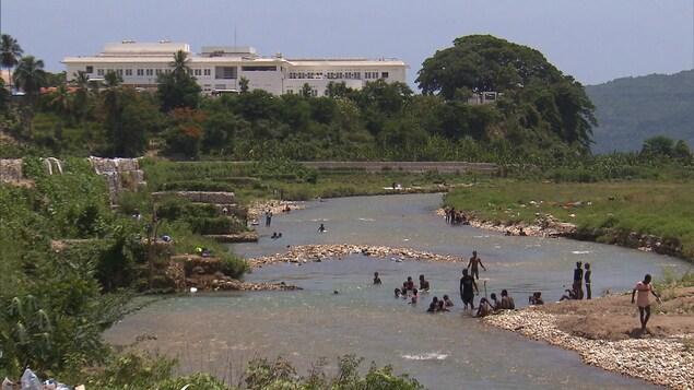 Des haïtiens se baignent dans un cours d'eau non loin de l'hôpital St-Michel de Jacmel.