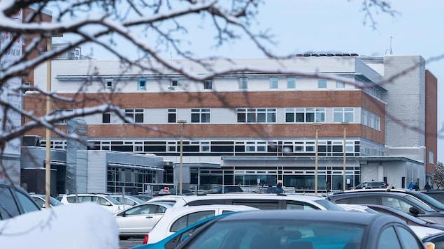 L'extérieur de l'hôpital et des voitures dans le stationnement, en hiver.