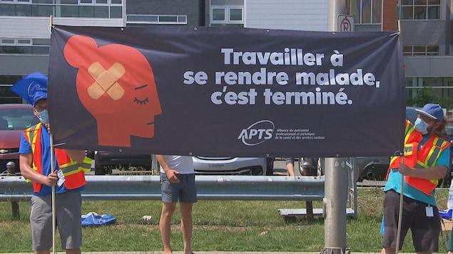 Des gens qui manifestent avec une pancarte devant l'hôpital à Trois-Rivières.