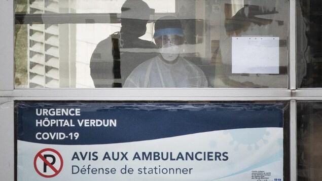 Des employés portant un masque derrière la porte vitrée de l'Urgence de l'Hôpital de Verdun.