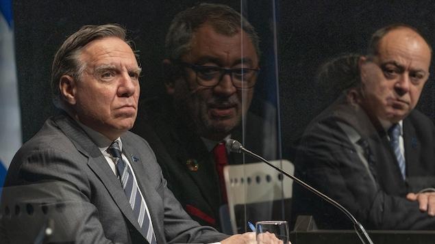 François Legault, Horacio Arruda et Christian Dubé assis durant un point de presse.