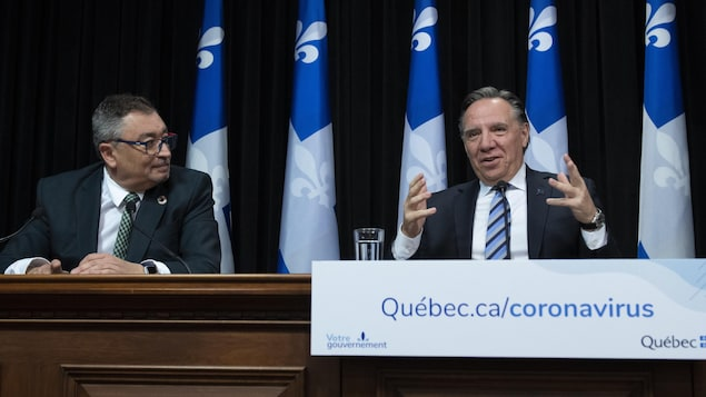 Horacio Arruda regarde François Legault qui parle lors d'une conférence de presse.