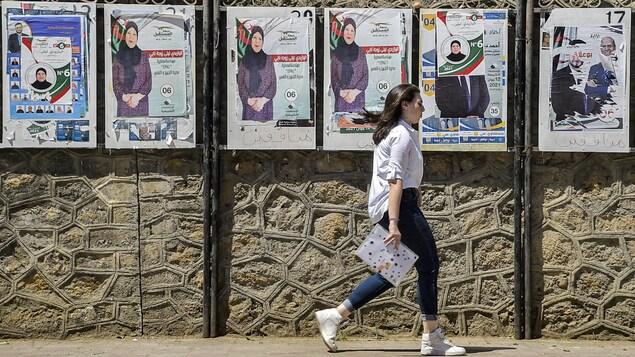 Une femme marche devant des affiches électorales.