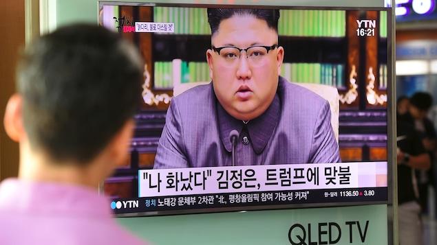 Un Nord-Coréen de dos regarde un écran de télévision sur lequel on voit Kim Jong-un.