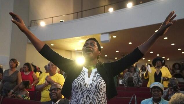 Une femme lève les bras au ciel pendant que le pasteur Jesse Jackson prononce son éloge funèbre lors de l'office à la mémoire d'Aretha Franklin.
