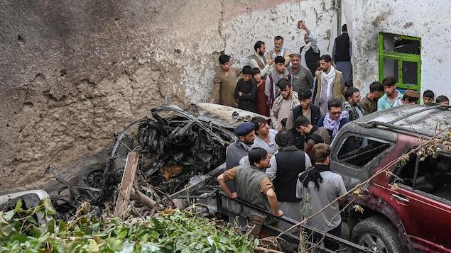 Des gens sont attroupés autour de la carcasse d'une voiture détruite par une explosion.