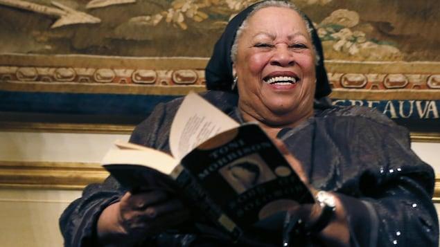 Une femme, tenant un livre, sourit.