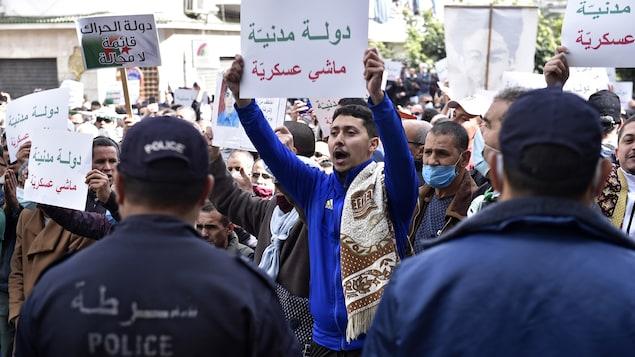 Des manifestants portant des pancartes face à des policiers.