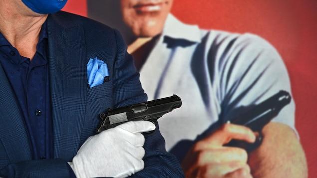 Un homme masqué et ganté tient un pistolet, devant une affiche de Sean Connery dans le rôle de James Bond tenant le même pistolet.