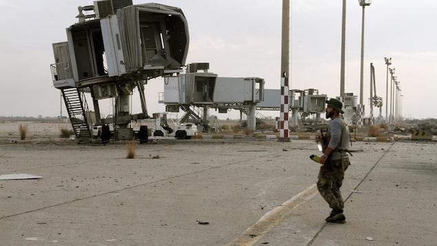 Un soldat sur le tarmac d'un aéroport endommagé.